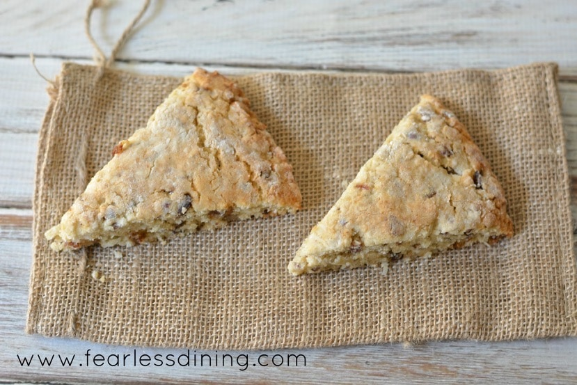 The top view of two Gluten Free Coconut, Date, and Pecan Scones on a small burlap bag. The scones are cut in triangle wedges.