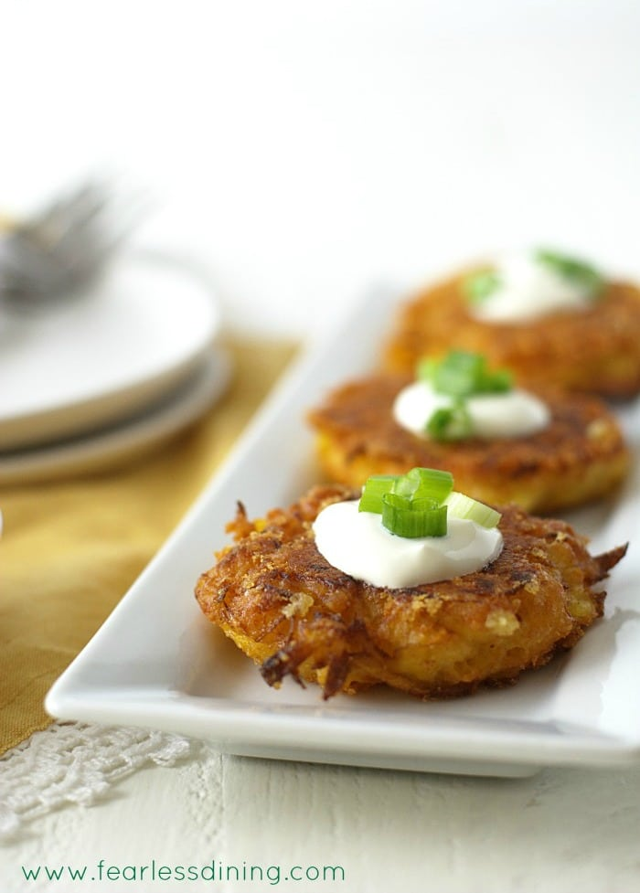 Gluten Free Delicata Squash Cheddar Fritters in a row on a rectangle plate
