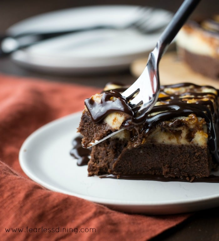 A fork scooping up a bite of Gluten Free Cheesecake Brownie Bars