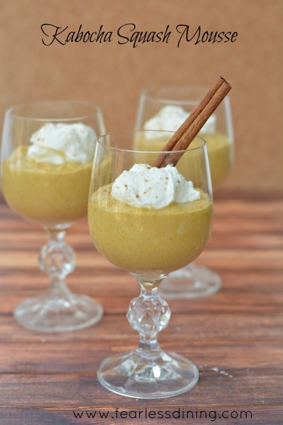 Kabocha Squash Mousse in tall wine glasses. The mousse has whipped cream and a cinnamon stick