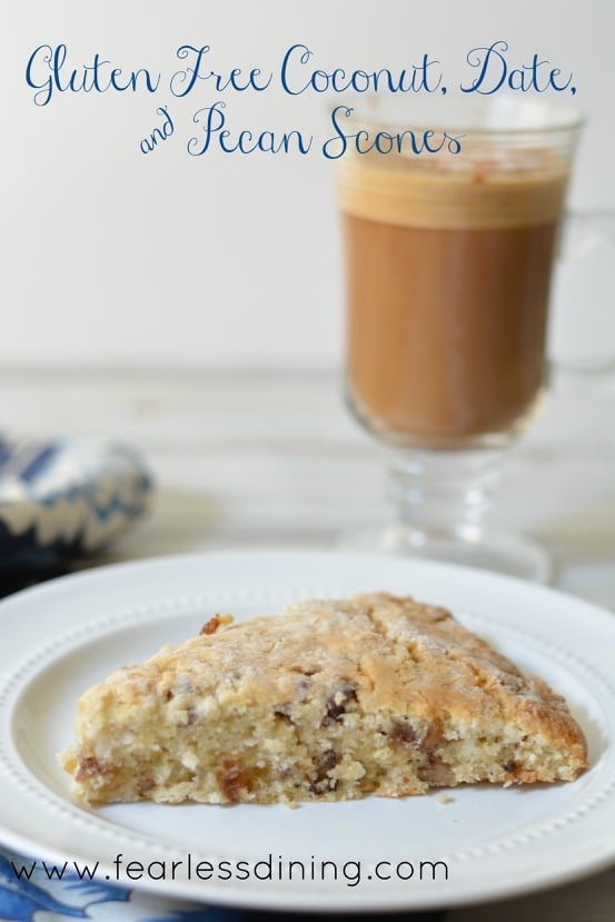 Gluten Free Coconut, Date, and Pecan Scone on a plate. A latte in a glass mug is in the background