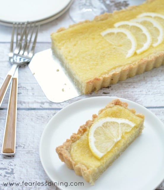 Gluten Free Lemon Tart slice on a plate with the whole tart behind it.