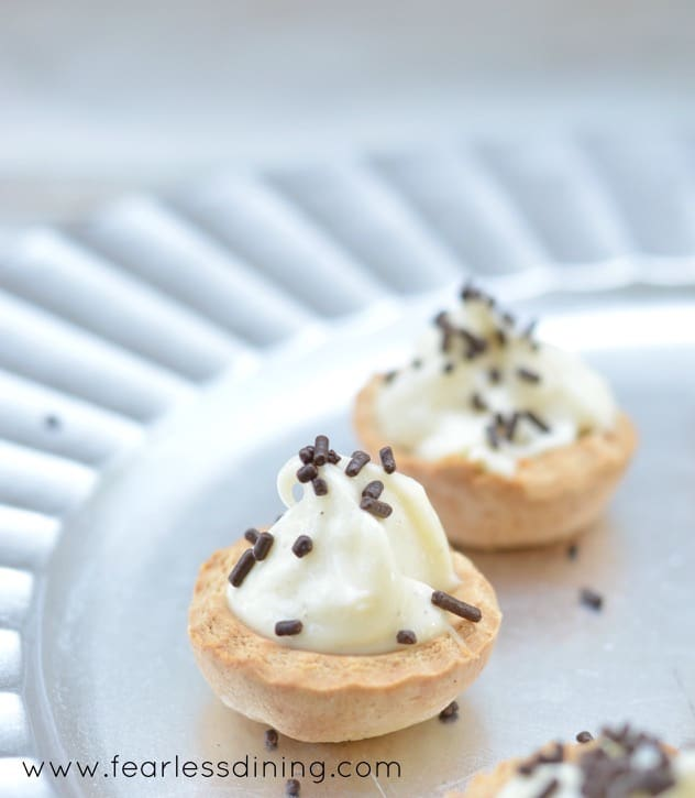 close up of two Gluten Free Baked Cannoli Bites with chocolate sprinkles on them. The cannoli cups are on a silver platter