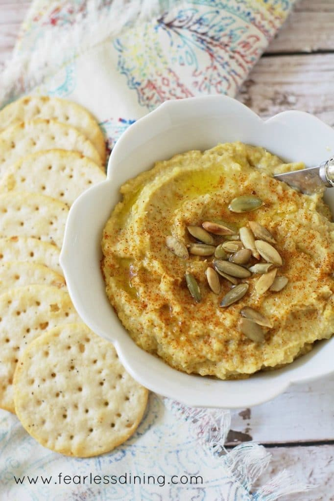 A white bowl of Hatch Chile Hummus with crackers around the bowl