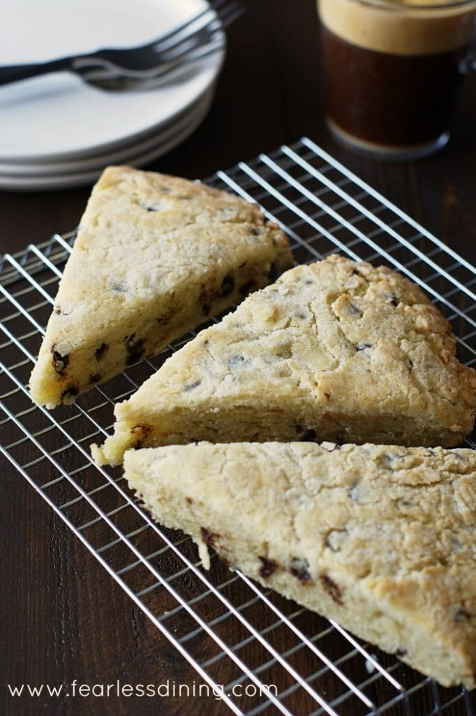 Gluten Free Eggnog Chocolate Chip Scones on a cooling rack with a coffee in the background