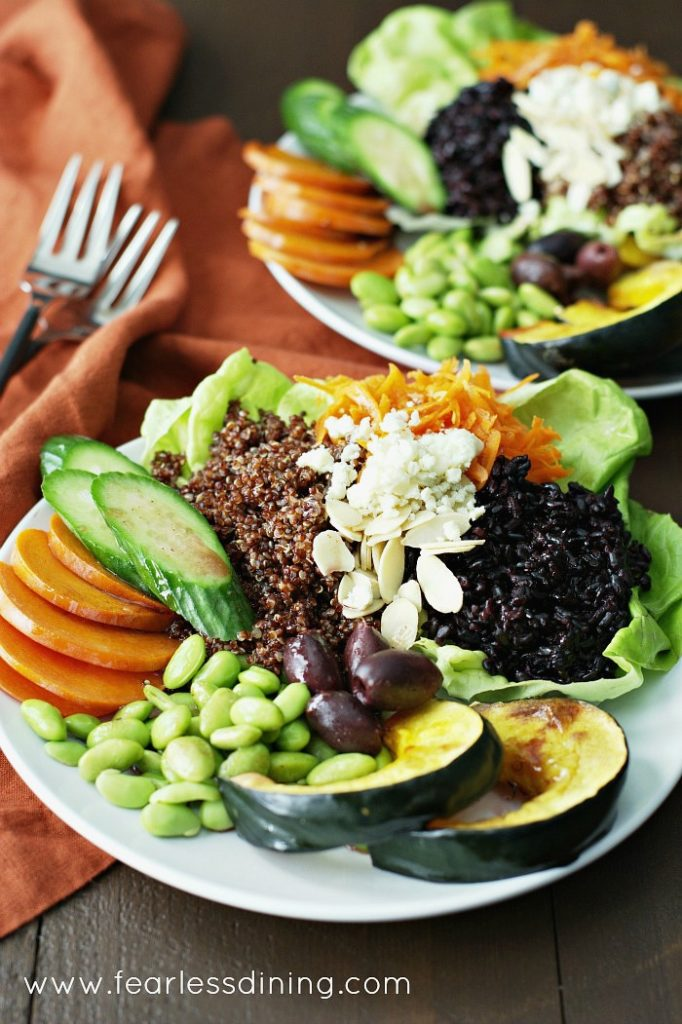 Black Rice and Quinoa Vegetable bowls on plates with an orange napkin and forks in the background