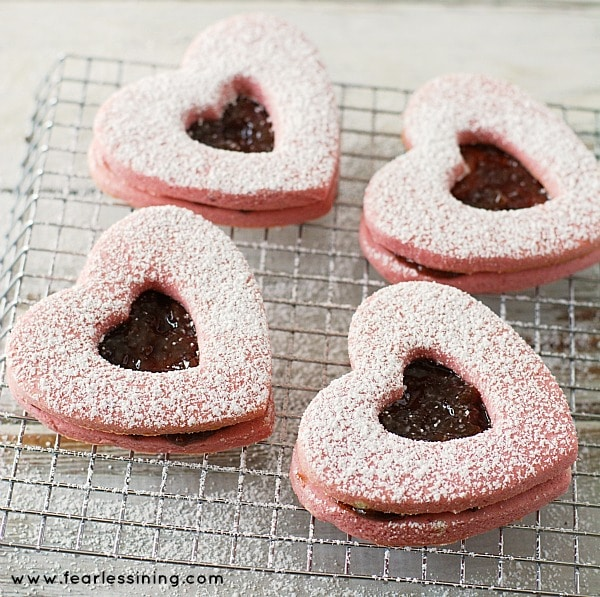 Gluten Free Heart Linzer Cookies on a rack with powdered sugar dusted on top