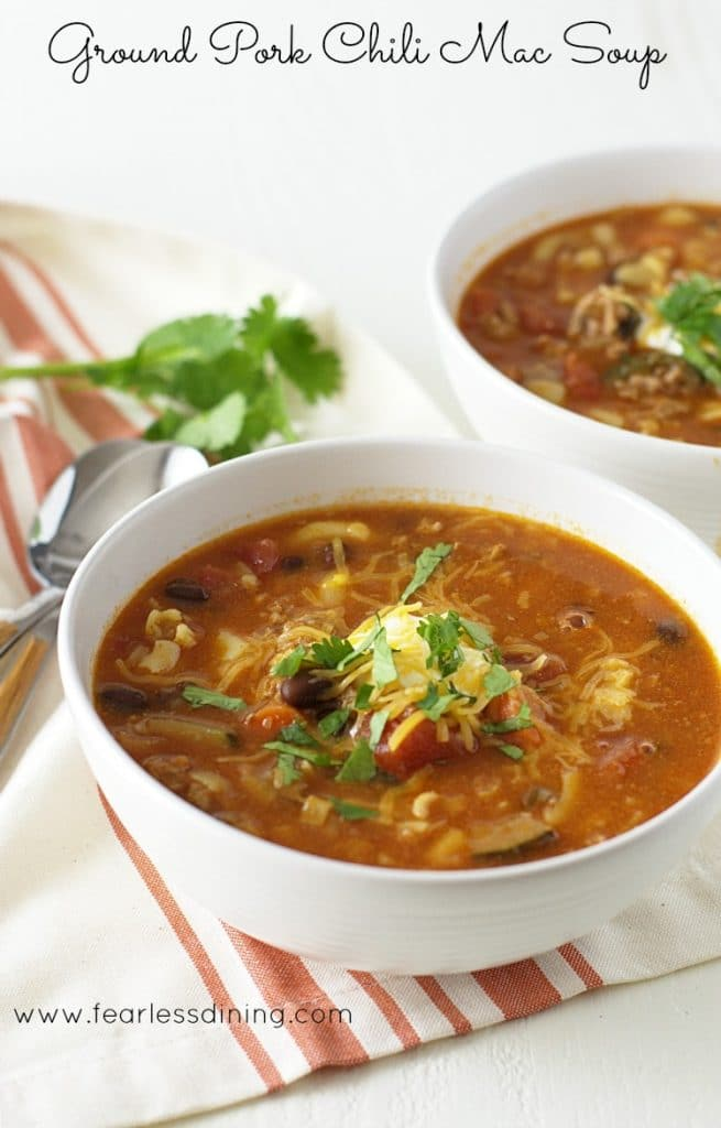 Two bowls of ground Pork Chili Macaroni Soup. Each bowl of soup is garnished with sour cream and cilantro