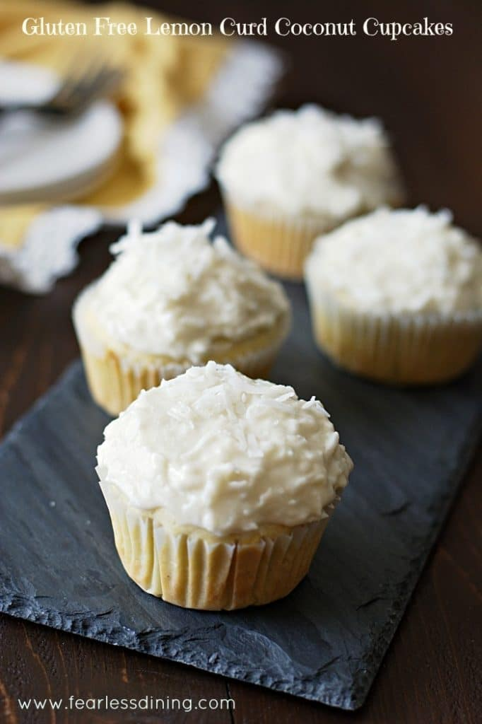 Gluten Free Lemon Curd Coconut Cupcakes with white frosting and shredded coconut. Cupcakes are on a slate tile