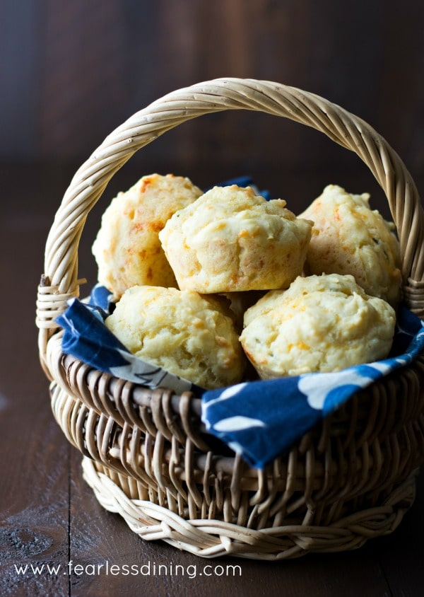 wicker basket holding gluten free savoury muffins with cheese and fresh herbs