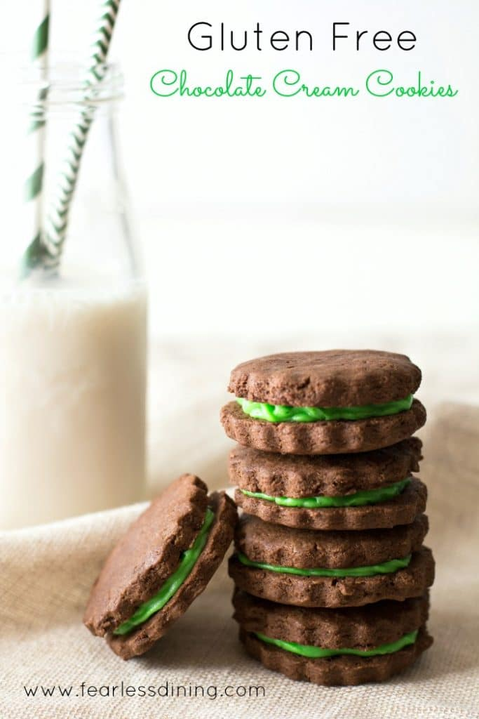 Gluten Free Chocolate Cream Cookies stacked on top of each other. One cookie is on its side. A glass of milk with green striped straws is in the background
