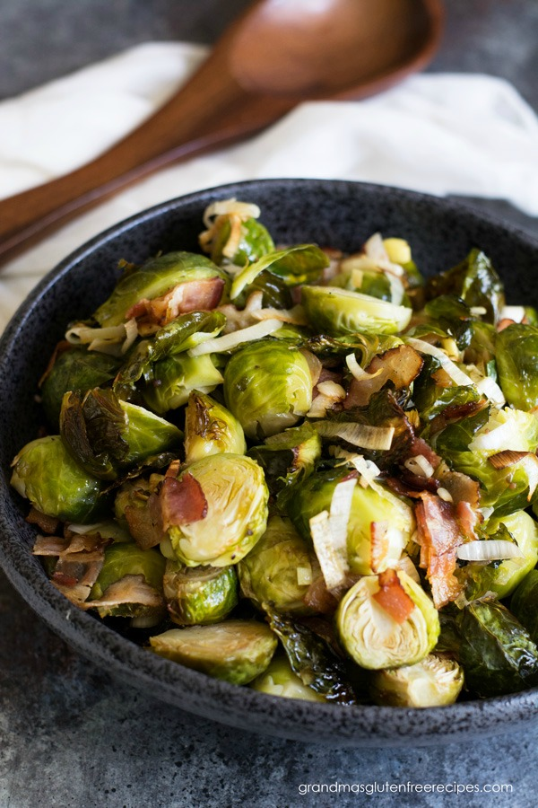 A bowl full of Brussels sprouts and bacon. A wooden spoon is next to the bowl.