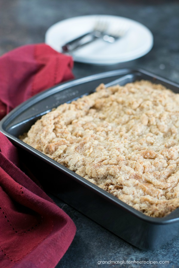 an 8x8 baking dish with gluten free crumb cake. A red napkin is to the side of the pan