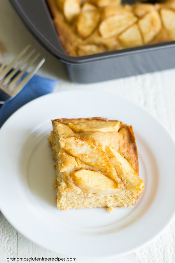A slice of German Apple Cake on a white plate. The cake pan is behind the plate.