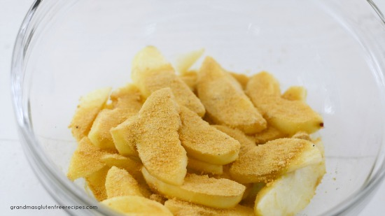 cut apple slices with blond coconut sugar and cinnamon in a bowl
