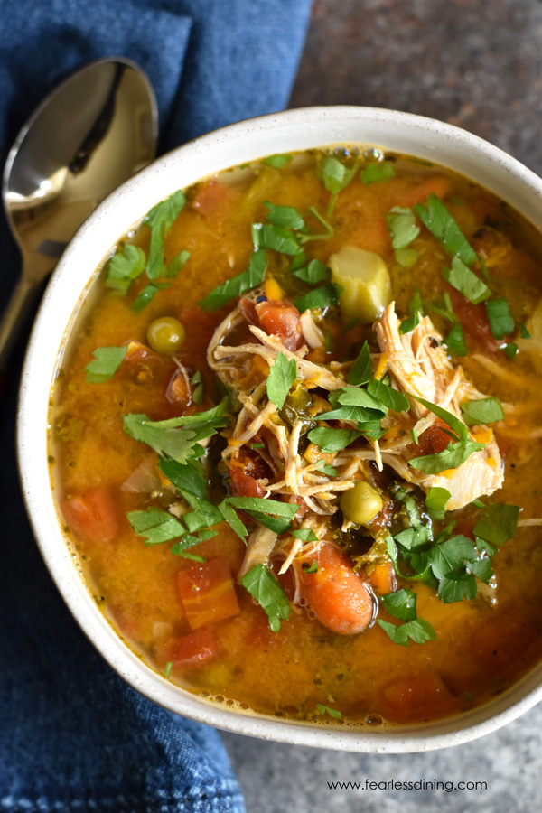 top view of a bowl of chicken vegetable soup. A blue napkin and spoon are next to the plate.