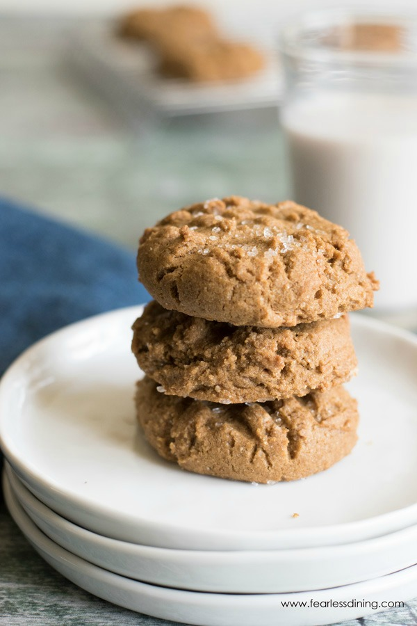 a stack of three molasses cookies on white plates. A glass of milk is behind the cookies